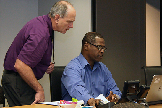 Entergy CEO Leo Denault (left) discussing GridEx with  Director of Incident Response Louis Dabdoub.